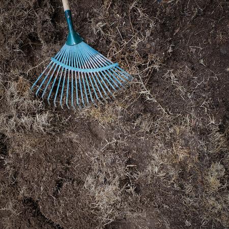 turf pile: yard work, preparation soil in garden with rake shoveling dry grass