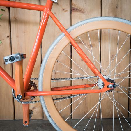 fixed: bicicleta fija del engranaje estacionado con la pared de madera, de cerca parte de la imagen de la bicicleta
