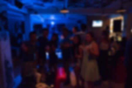 nightclub crowd: image blurred background, group of young people having joyful dancing in nightclub party Stock Photo