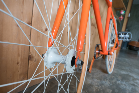 machine teeth: fixed gear bicycle parked with wood wall, close up image part of bicycle