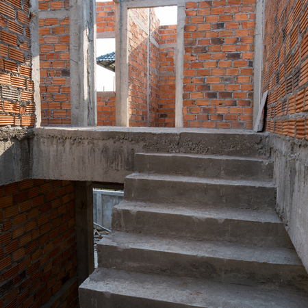housebuilding: staircase cement concrete structure and brick wall in residential house building of construction site industry
