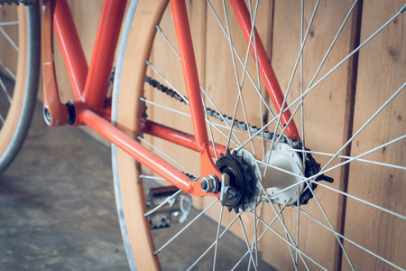 dirty teeth: fixed gear bicycle parked with wood wall, close up image part of bicycle