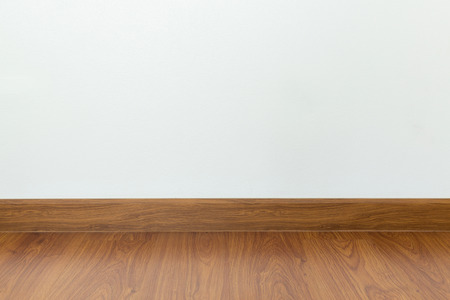 wood laminate: empty room with brown wood laminate floor and white mortar wall background