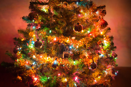 christmas background, christmas tree decorated with twinkling light and christmas ornament in home Archivio Fotografico