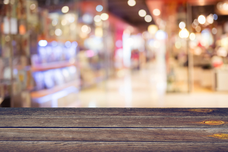 departmentstore: empty blank wood table and colorful blur department store shopping mall background
