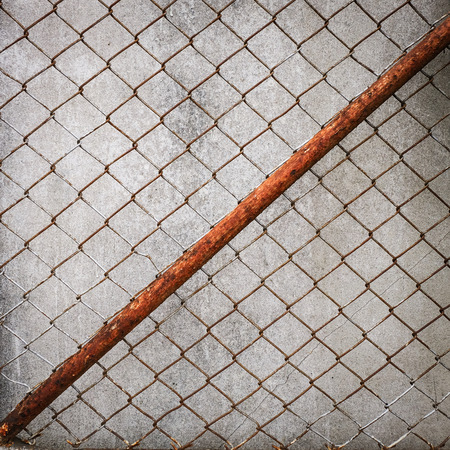 metal wall: rusty iron chain wire fence on cement wall background Stock Photo