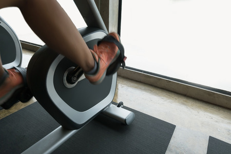 fitness woman: woman exercise riding bicycle in fitness center, activity of healthy care Stock Photo