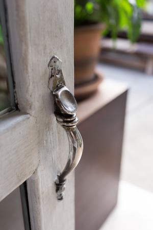 puertas de hierro: abrir la puerta, primer plano estilo de tirador de la puerta antigua de la vendimia en la puerta de madera blanca