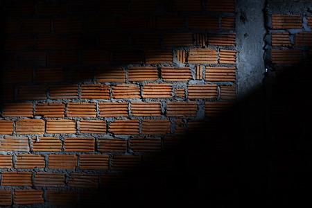 materiales de construccion: pared de ladrillos en el sitio de construcci�n de viviendas con sol luz a trav�s de la ventana