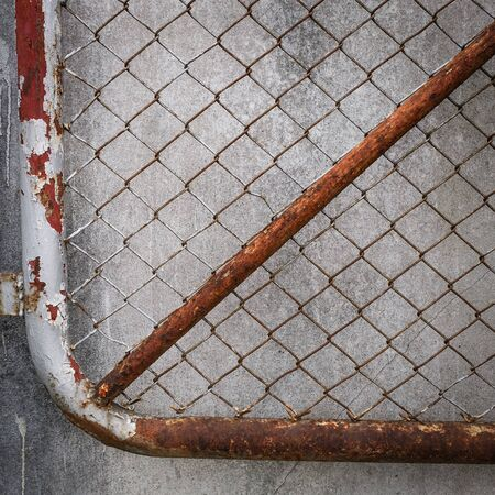 enclose: rusty iron chain wire fence on cement wall background Stock Photo