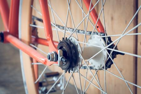 clavados: bicicleta fija del engranaje estacionado con la pared de madera, de cerca parte de la imagen de la bicicleta