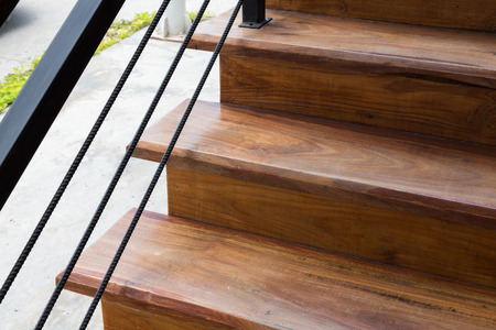 banister: brown wooden staircase with iron banister in modern house Stock Photo
