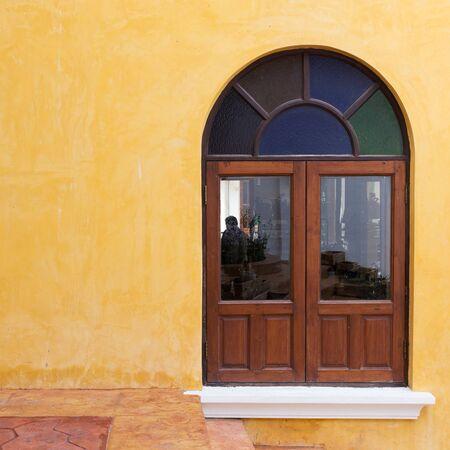 wood door: fen�tre en bois sur le ciment jaune mur de mortier de fond