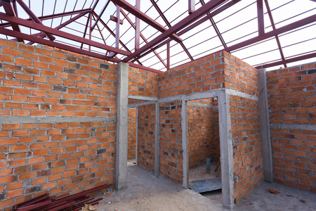 roof beam: structural steel beam on roof and brick wall of building residential construction Stock Photo