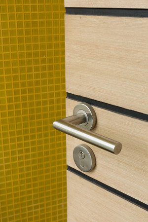 key hole: door handle and  key hole on wooden door with yellow tiles wall background Stock Photo