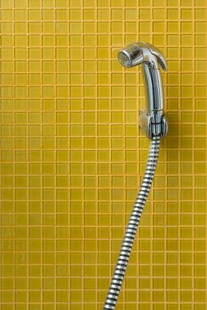 latrine: bidet shower, bidet spray in toilet with yellow tile wall