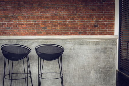 bar stool: design of interior, counter bar made from cement with iron seat bar stool and brick wall background Stock Photo