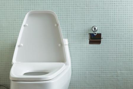 Witte flush toilet en gele muur mozaïek decoratie in moderne
