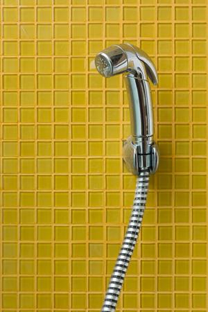 bidet: bidet shower, bidet spray in toilet with yellow tile wall