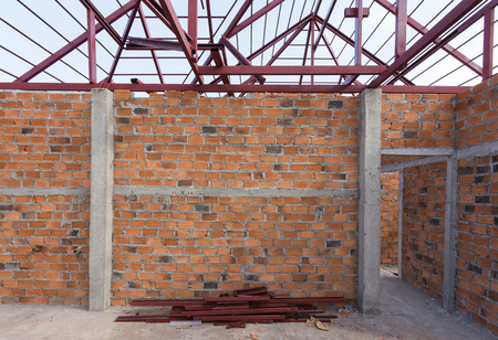 housebuilding: structural steel beam on roof and brick wall of building residential construction Stock Photo