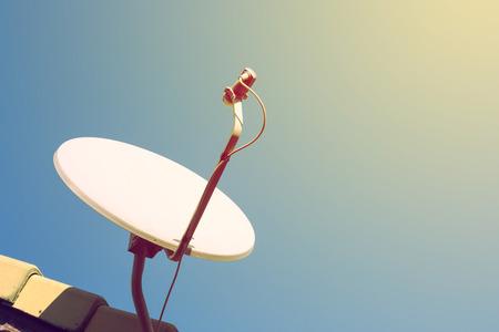schotelantenne en tv-antennes op het huis dak met blauwe hemel achtergrond Stockfoto