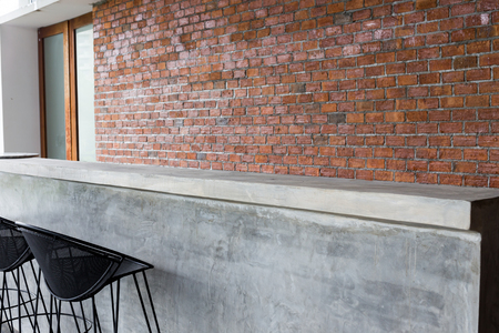 barstool: design of interior, counter bar made from cement with iron seat bar stool and brick wall background Stock Photo
