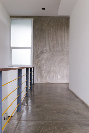 passageway: architecture design of house, passageway cement floor and white wall with baluster in modern room