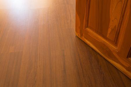 on wood floor: wood laminate floor and wooden door open