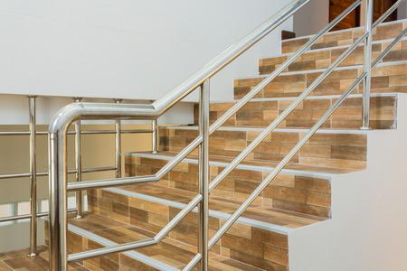 escalera en casa residencial con pasamanos de acero inoxidable, piso de cerámica azulejos de madera del modelo Foto de archivo