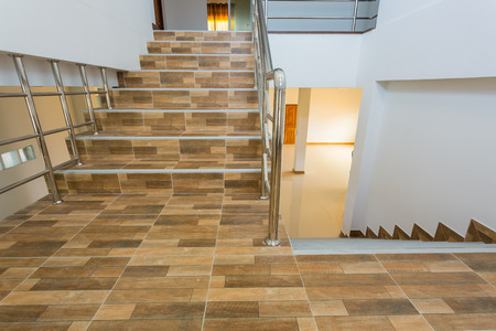 escalera en casa residencial con pasamanos de acero inoxidable, piso de cerámica azulejos de madera del modelo