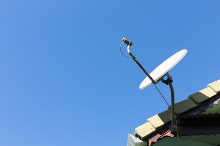 Satellitenschüssel und TV-Antennen auf dem Hausdach mit blauem Himmel im Hintergrund