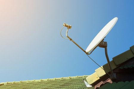 satellite: satellite dish and TV antennas on the house roof with blue sky background