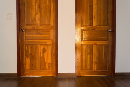 white wood floor: wood door in empty room, white mortar wall background and wood laminate floor in residential Stock Photo