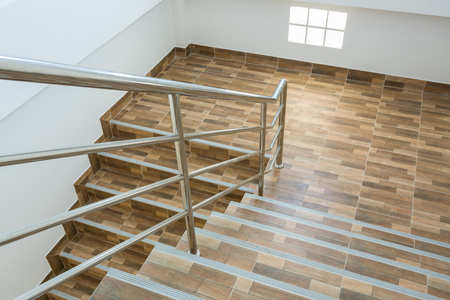 staircase in residential house with stainless steel banister, ceramic floor tiles wood pattern