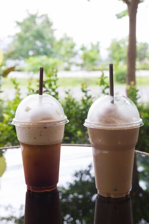 restaurant tables: cold ice coffee drink put on glass table in the garden
