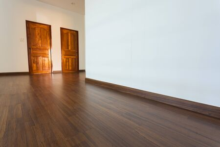 white wood floor: empty room, white mortar wall background and wood laminate floor in residential Stock Photo