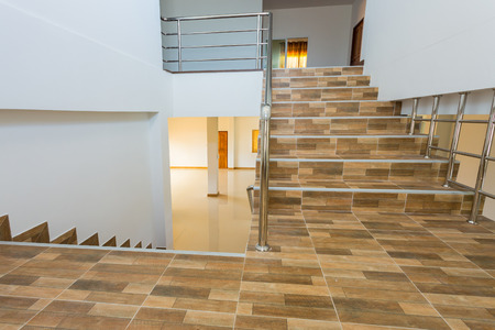 banister: staircase in residential house with stainless steel banister, ceramic floor tiles wood pattern