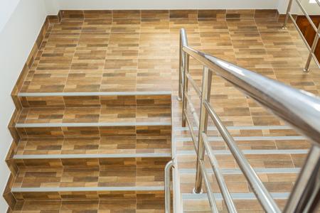 trap in woonhuis met roestvrij stalen leuning, keramische vloertegels houtmotief