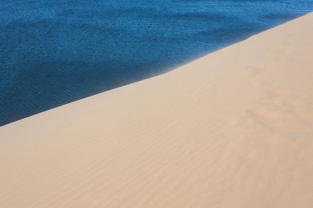 ne: footprint on white sand dune desert and lake in Mui Ne, Vietnam