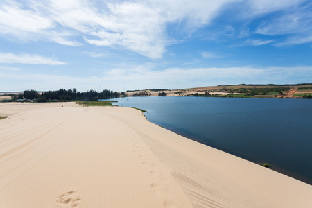 ne: footprint on white sand dune desert and lake in Mui Ne, Vietnam