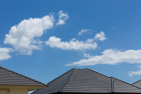 black tile roof on house with clear blue sky and cloud background