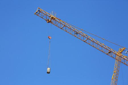 hook up: construction crane hoisting cement bucket mixer pouring Stock Photo