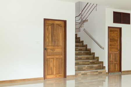 room door: white empty room interior with wooden door and staircase