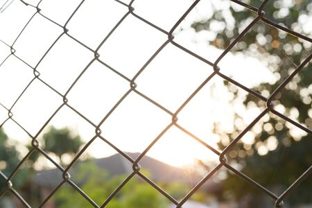 enclose: steel wire mesh fence with sunlight background Stock Photo