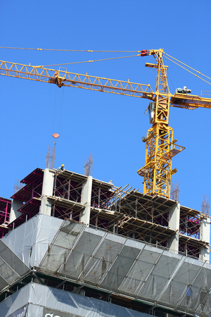 laborer: construction site building industry with machinery crane working and laborer worker