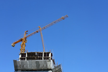 machinery crane working in construction site building industry with blue sky background