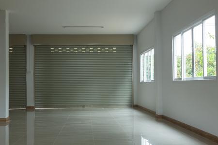 habitación vacía en la casa de edificio de viviendas con puerta de persiana de aluminio y vidrio de ventana deslizante y suelos de baldosas blanco
