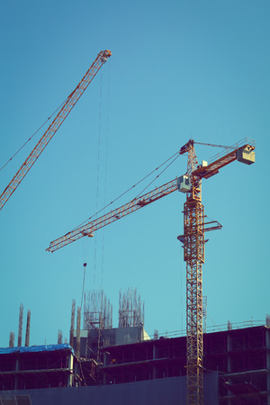 machinery crane working in construction site building industry with blue sky background, image used filter effect  vintage