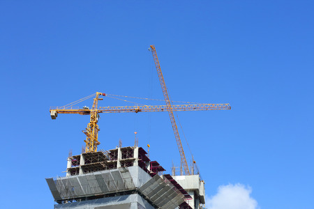 machinery crane in construction site building industry with clear blue sky background