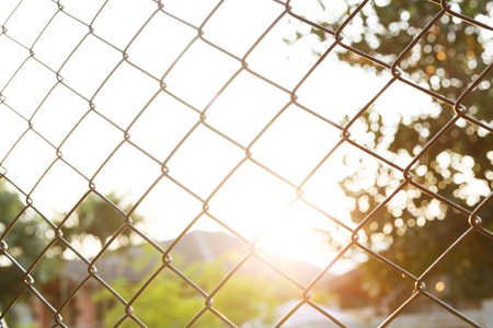 chainlink fence: steel wire mesh fence with sunlight background Stock Photo